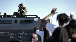 A member of the St. Louis County Police Department points his weapon in the direction of a group of protesters in Ferguson, Missouri